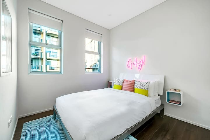 Vibrant and spacious, the third bedroom boasts a plush queen bed, floating side tables and a neon pink sign.