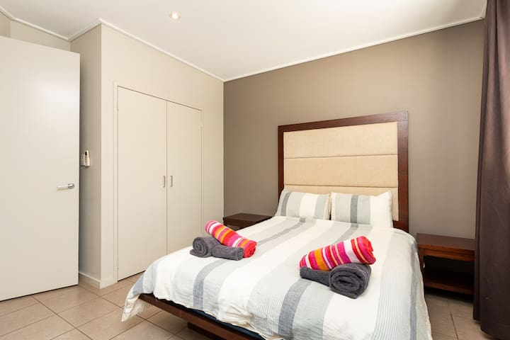 Separate bedroom with queen size bed & storage space