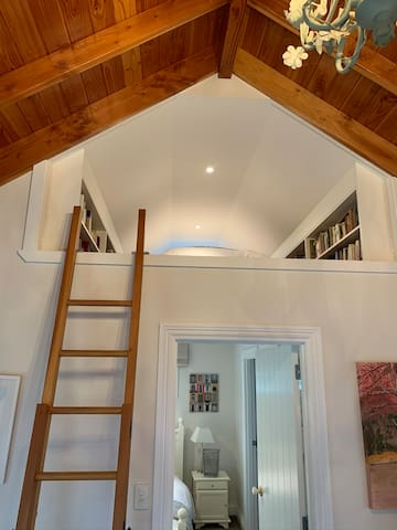 A wooden ladder leads up to the third bedroom.