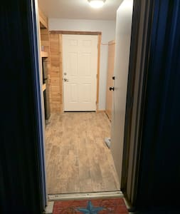 When you enter you will be in the entry storage area. Light is on the left and entrance to the unit is on the right. Refrigerator is near the other door. This door is access to our garage and is locked and not accessible.