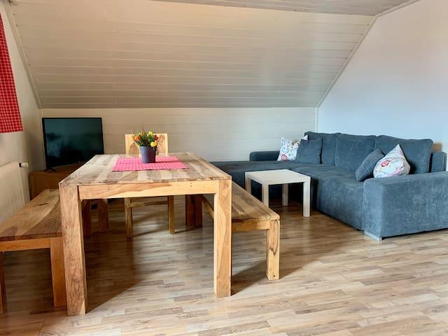 Wohnzimmer mit Esstisch und Schlafcouch.