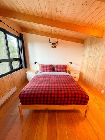 Bedroom in the bunkhouse with a queen bed and an incredible view!