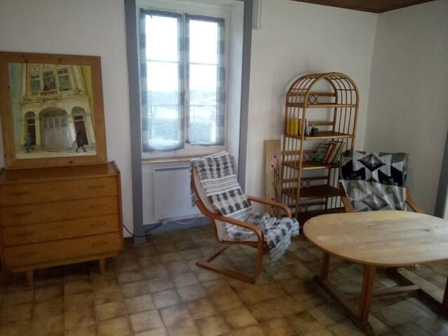 coin salon avec table basse, deux fauteuils et un canapé ainsi qu'une petite commode et quelques livres, BD, jeux de société....