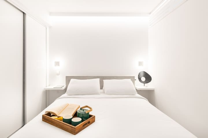 Master Bedroom A White tones, hidden lighting, reading lights, a king size bed with anatomical Coco-Mat mattress and pillows. Organize your clothes  in the spacious closet, use the blackout curtain and air conditioning  and experience the relaxation.