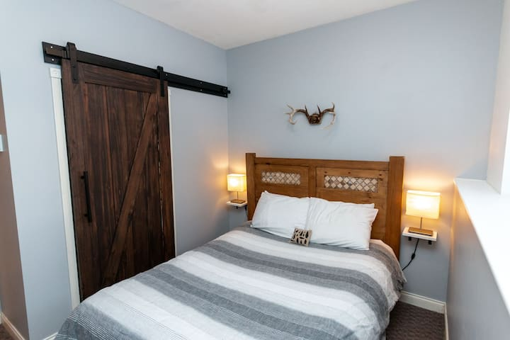 Master bedroom with queen-size bed and all natural linens.  Barn-style door slides to gain access to large closet.