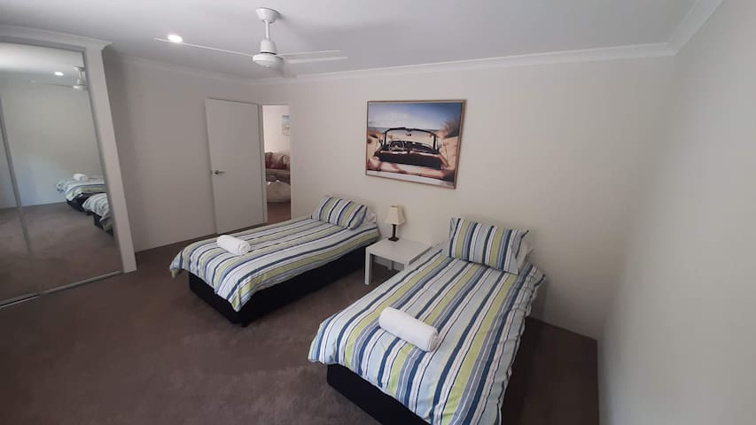 The fourth bedroom features two single beds and a view of native Australian bush