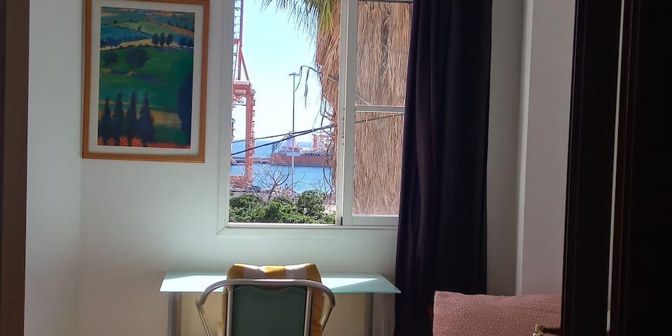 Habitación con cama individual 80x200, escritorio, armario y ventana con vistas al mar.