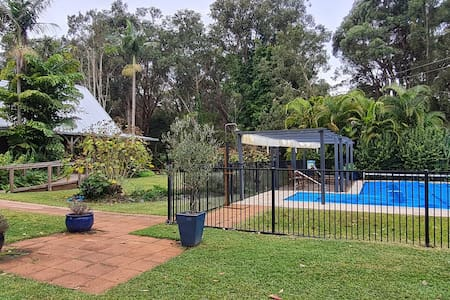 Flat 120 cm wide paved pathway from car landing paved area to same width gently sloping ramp to front entrance. All dimensions meet accessibility standards. Note pathway extends into pool area.