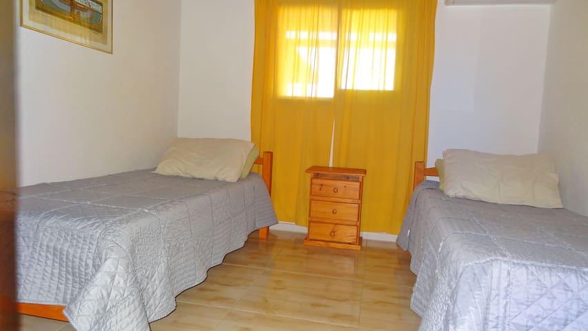 Room two with two single beds and a spacious wardrobe. There is also an air conditioner.  Habitación dos con dos camas individuales y un amplio armario.  También hay aire acondicionado.