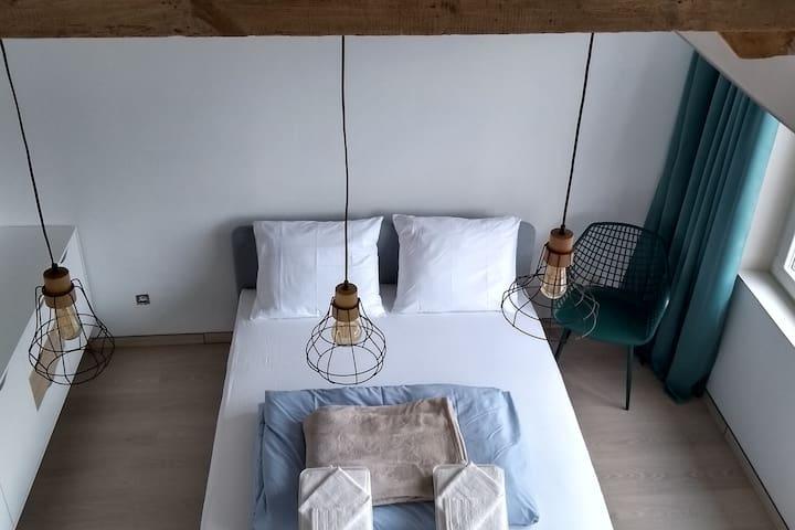 ruime en lichte slaapkamer met het houten dakgebinte