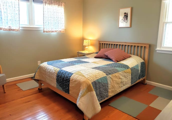 The master bedroom - a patchwork quilt tops a queen size bed with wooden bed frame.