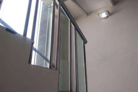 Pasamano y lámpara en la escalera que lleva al cuarto.