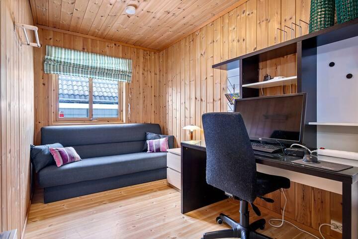 Rommet inneholder også en arbeidsplass med Chromebox. Sovesofaen gjøres om til en 120 cm bred enkeltseng.