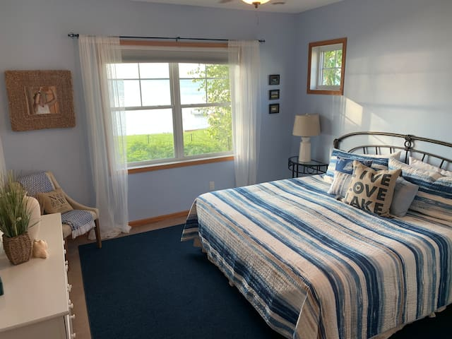 Main floor master bedroom with a king size bed and fantastic lake views.