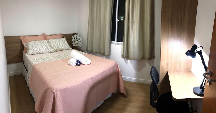 Segundo quarto com cama de casal, maleiro, uma pequena bancada de trabalho e ar condicionado. Roupas de cama, toalha em alta gramatura e sabonete.