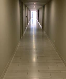 Pasillo de acceso al apartamento amplio, plano, buena iluminación y con elevadores.