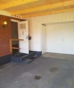 Carport och belyst ingång till källarvåningen