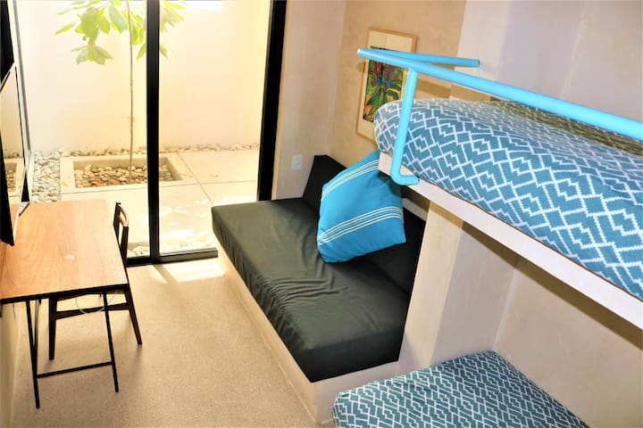 Third bedroom has 3 additional single beds.  Sleeps 7 total in the house.  Also has a large smart TV and desk for a comfortable workspace.