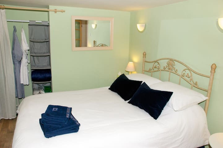 Private bedroom . 4'6'' double bed. Fresh linen, duvet , 4 pillows, towels ,robes and slippers provided. Ample hanging and clothes storage space . Extra blankets /throws. Hairdryer.Night light, USB sockets , TV , alarm clock.