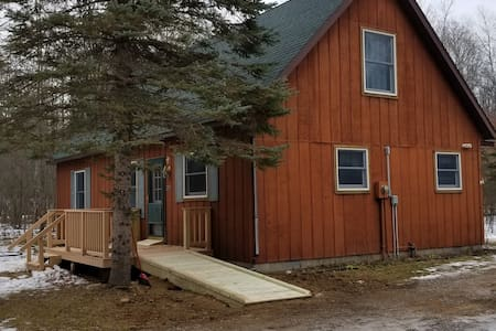 you can park by the ramp and lower your lift gate if so equipped right to the ramp. there is a slight elevation to the ramp and a small ramp to enter the door. the main floor of the house is all flat, carpet in the bedroom and area rug in the living