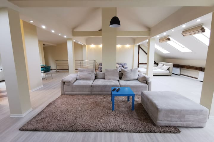 Open space upper floor consisting of living room area and a sleeping area in the back