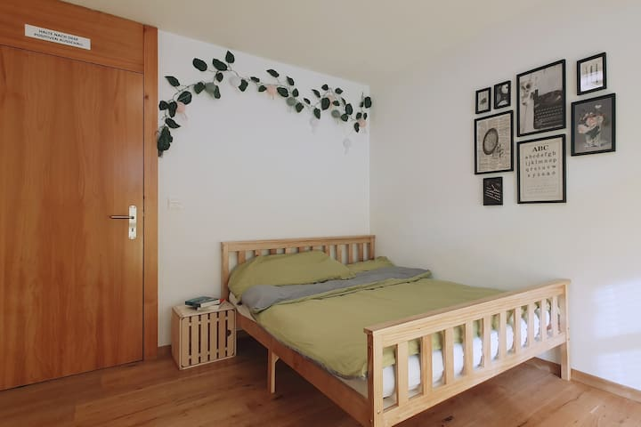 Schlafzimmer mit Doppelbett, Kleiderschrank und Schreibtisch sowie Zugang zum Balkon
