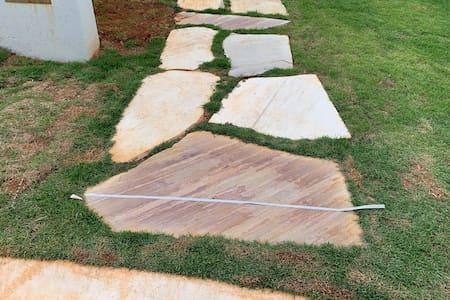 Um caminho grande o bastante para entrar com a cadeira, mas necessita de ajuda de outra pessoa pois tem meio fio e as pedras podem ser um pouco desniveladas.