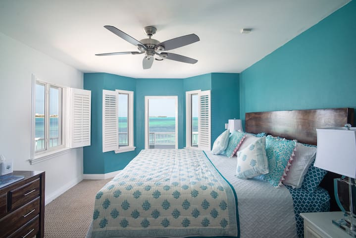 This first-floor master bedroom consists of a king-sized bed, an ensuite bathroom, and an amazing patio with the best view.