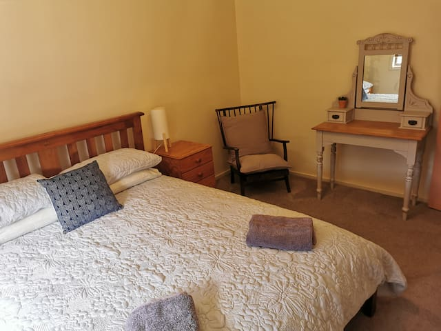 Queen bedroom with mirror on dressing table.