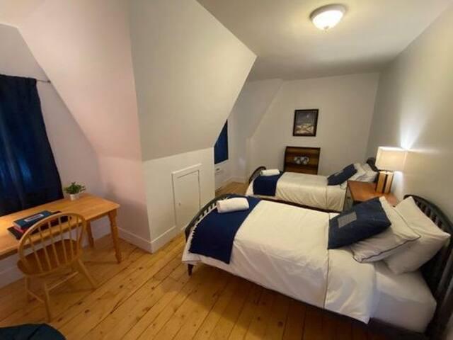 Chambre à coucher deux lits simples et un espace bureau. Quelques jeux de société pour amuser vos soirées!