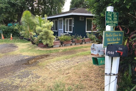 Designated parking spot for Ohia Kai Cottage is directly in front of the cottage. Area is unpaved but flat, with compacted dirt, grass, and gravel.