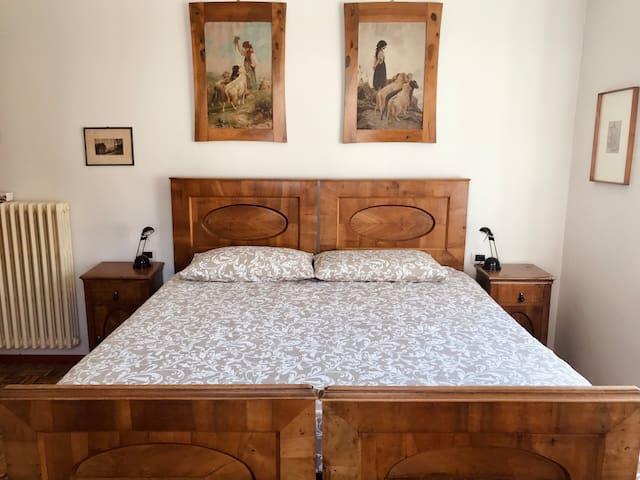 L'arredamento di CAMERA DA LETTO 2, la più grande, è in stile impero, con letto e quadri d'epoca originali.  Per addormentarsi in una atmosfera oltre tempo.