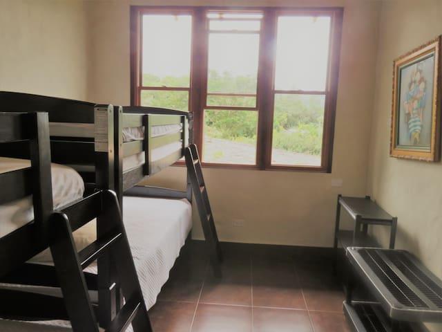 Vista de 4o cuarto; Dos camas camarotes.  Ventanas con vista a la parte trasera de la propiedad