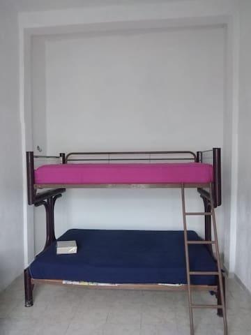 Recámara planta baja, con una lintera de cama matrimonial e individual, y un hamaqueros y ventilador