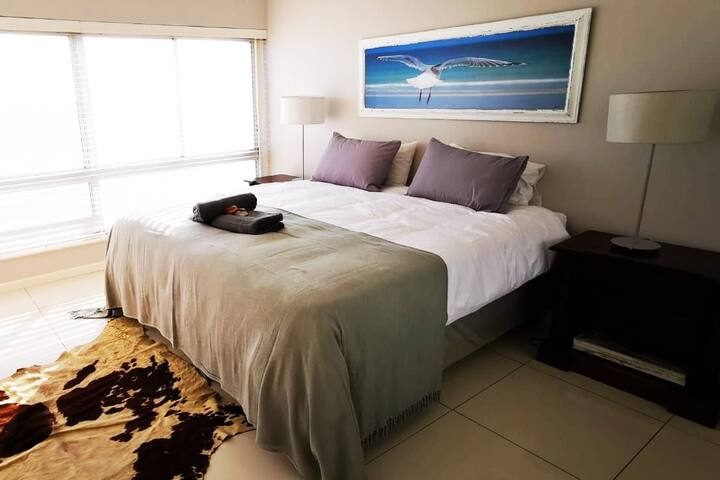 Spacious main bedroom with breathtaking views of Table Mountain and the ocean