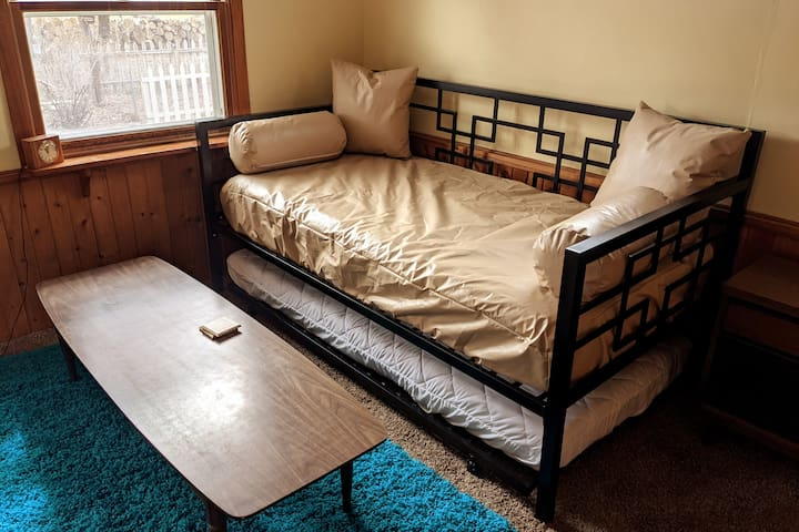 Our third bedroom has a daybed with trundle, which can be made up if needed into two comfortable beds. It also serves as an inviting rec room, with a record player, table and view of your private backyard.