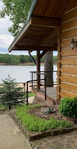 Railing and entrance to the cabin via the covered front porch up 2 steps