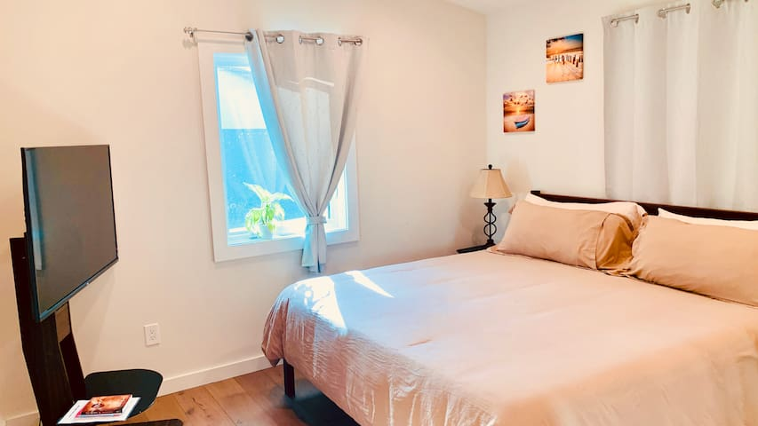 """The master bedroom is designed in gold & beige. It makes the room warm & comfy. These colors were appointment to reflect the colors of Athens in ancient Greece. The kind bed is comfy & has 4 king-sized pillows. We also have a 50"""" SmartTV"""