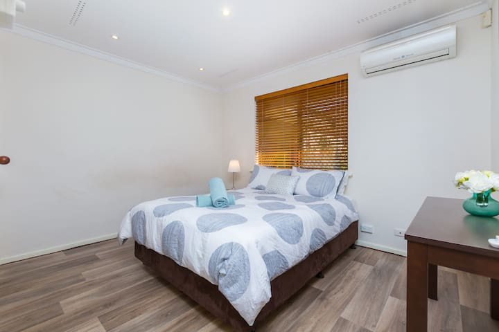 The main bedroom - complete with queen bed, wardrobe for your belongings & heating & cooling unit to keep you warm & cool all year long!