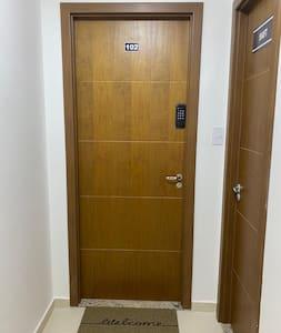 Porta de entrada, antes dela, apenas corredor do elevador e hall de entrada amplo