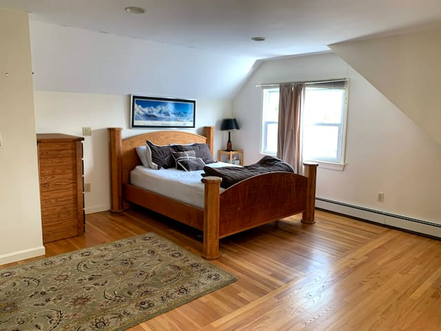 Large Master bedroom with Queen bed, large windows and A/C window unit.