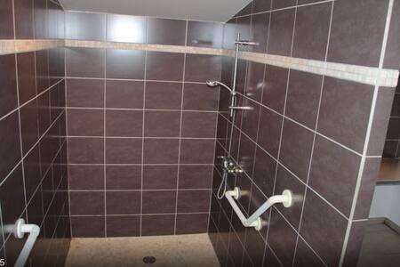 Douche à l'italienne spacieuse avec rampes.