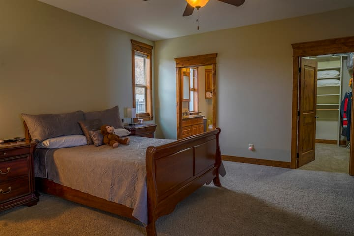 Master bedroom with queen bed, walk-in closet, and attached master bathroom in main house