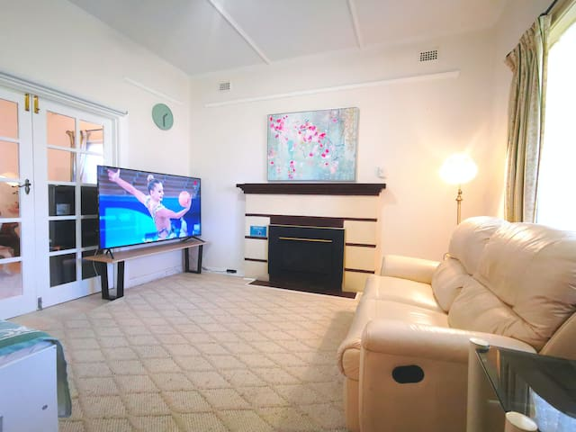 """Another spacious lounge with 2-seat recliner and 70"""" Smart TV. The electric fireplace keeps your family warm during winter days."""