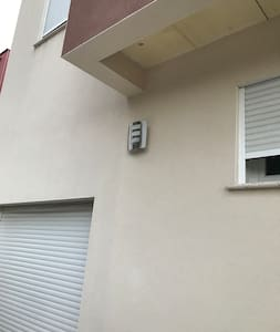 Lumière à détecteur de mouvements devant la maison. La porte d'entrée est également éclairée par le lampadaire de la rue