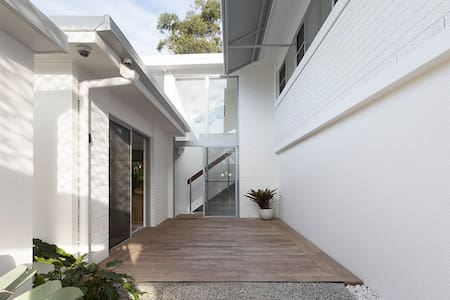 Soul Beach House front entry timber deck features recessed glass sliding doors to the entry and to the kitchen, ensuring level thresholds throughout. The concrete pathway from the front carport to the front deck has only a slight incline.