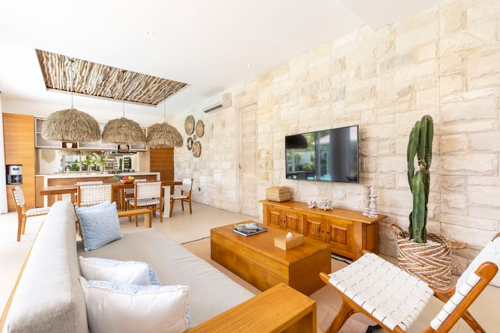 Spacious, comfy and super relaxing living room with 4K smart TV, swimming pool view and open dining and kitchen area