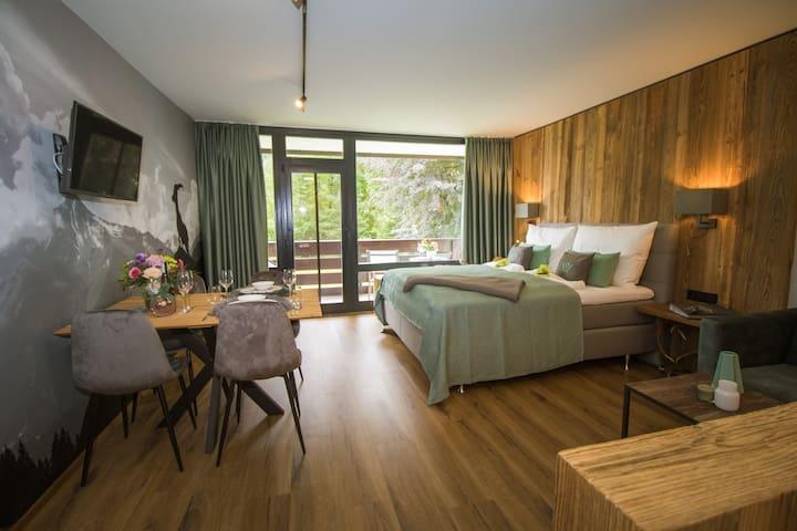 Wohnzimmer Essbereich und Boxspringbett und Smart-TV