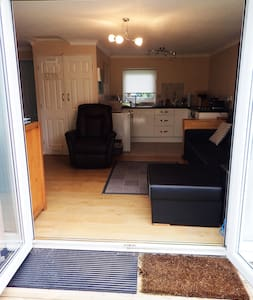Main entrance to chalet through wide patio doors. Car parking is close to the ramp on even tarmac surface. No curbs or steps to get to the ramp.  The car park area is not marked disabled, as  our other guests  need to park there. Plenty of parking.