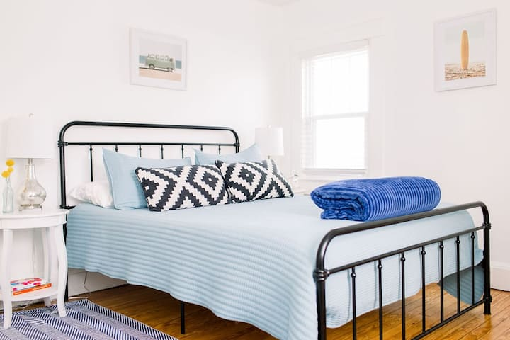 The blue bedroom has a queen-sized bed, dresser, closet, usb lamps, and google mini.